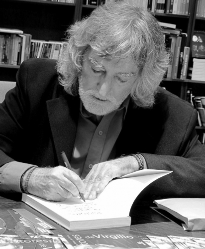 Em foto preta e branca, Álvaro Alves Ferreira autografa um livro em frente à sua instante particular